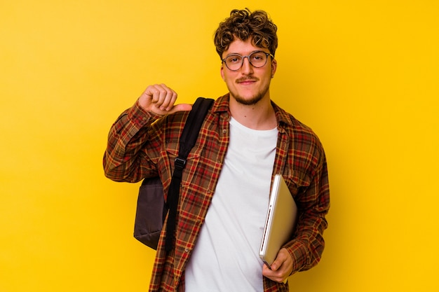 Young student caucasian man holding a laptop isolated on yellow background feels proud and self confident, example to follow.