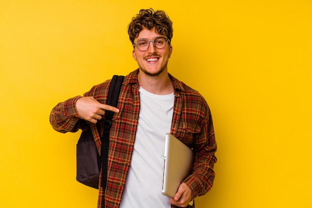 Young student caucasian man holding a laptop isolated on yellow background person pointing by hand to a shirt copy space, proud and confident