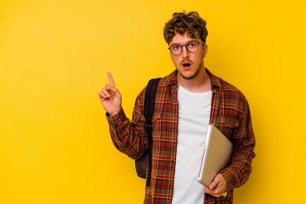Young student caucasian man holding a laptop isolated on yellow background pointing to the side