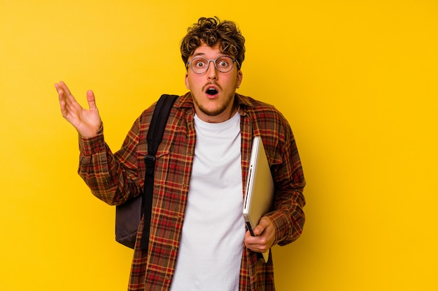 Young student caucasian man holding a laptop isolated on yellow background surprised and shocked.