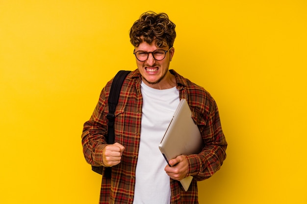 Young student caucasian man holding a laptop isolated on yellow wall screaming very angry and aggressive.