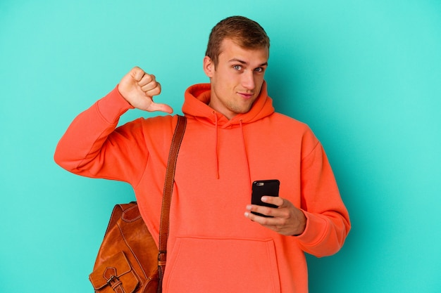 Young student caucasian man holding a mobile phone isolated on blue feels proud and self confident, example to follow.