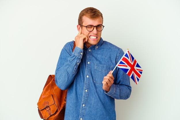 젊은 학생 백인 남자 손으로 귀를 덮고 흰색 절연 영어 공부.