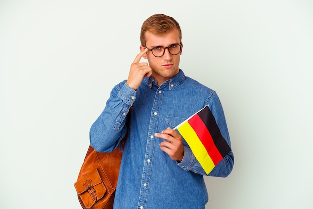 손가락으로 사원을 가리키는 흰 벽에 고립 된 독일어 공부 젊은 학생 백인 남자 생각, 작업에 초점을 맞춘.