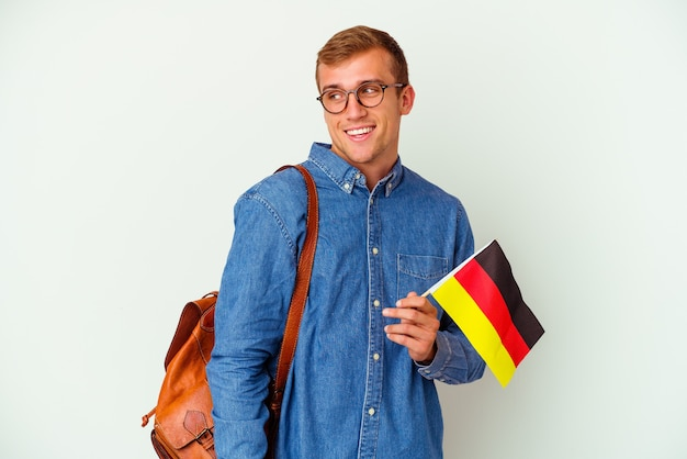 Young student caucasian man studying german isolated on white looks aside smiling, cheerful and pleasant.