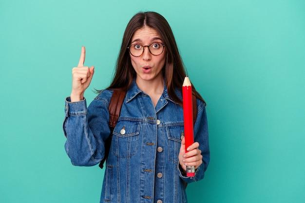 いくつかの素晴らしいアイデア、創造性の概念を持っている青い背景に分離された大きな鉛筆を持っている若い学生白人女性。