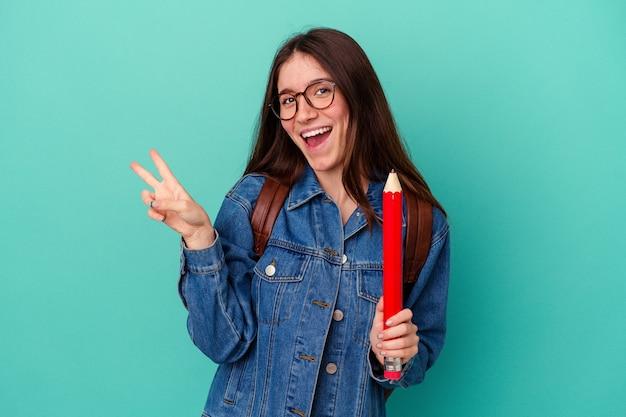 青の背景に分離された大きな鉛筆を持っている若い学生の白人女性は、指で平和のシンボルを喜んで気楽に示しています。