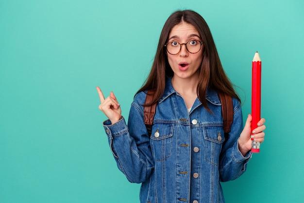 側面を指している青い背景で隔離の大きな鉛筆を保持している若い学生白人女性