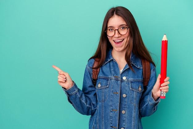 青い背景に分離された大きな鉛筆を持って笑顔で脇を指して、空白のスペースで何かを示している若い学生の白人女性。