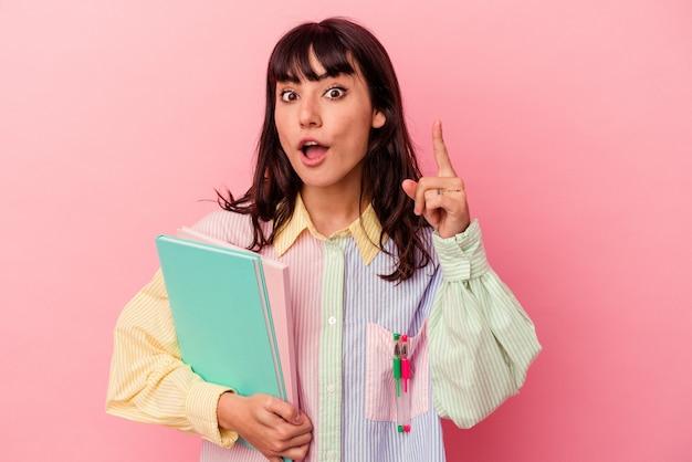 ピンクの背景にアイデア、インスピレーションのコンセプトを持つ本を保持している若い学生の白人女性。