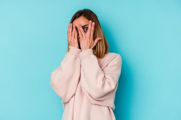 Молодая студентка кавказской изолирована на синей стене, моргает сквозь пальцы испуганно и нервно