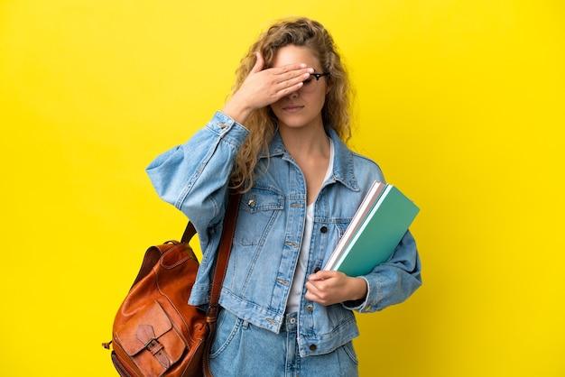 Женщина молодого студента кавказская изолированная на желтом фоне, закрывая глаза руками. не хочу что-то видеть