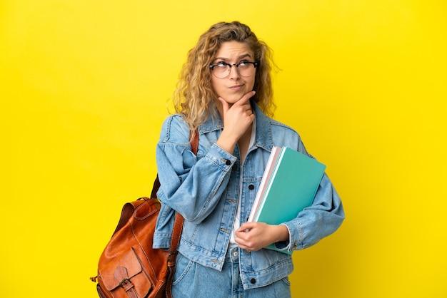 Молодая студентка кавказской женщины изолирована на желтом фоне, сомневаясь