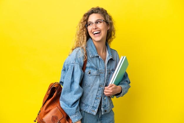 Молодой студент кавказской женщина изолирована на желтом фоне смотрит в сторону и улыбается