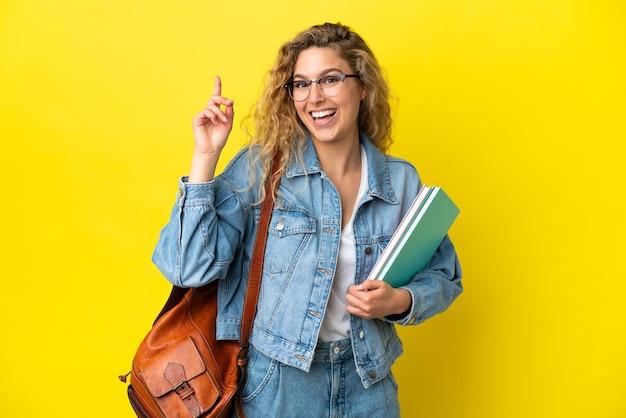 Молодая студентка кавказская женщина изолирована на желтом фоне, указывая вверх отличную идею