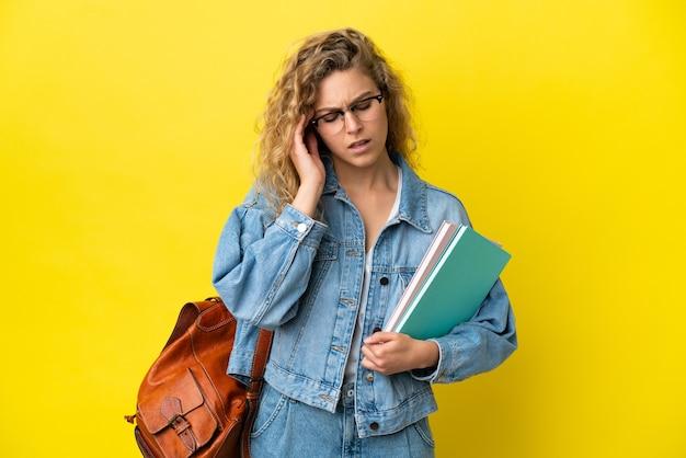 Молодая студентка кавказской женщины изолирована на желтом фоне с головной болью