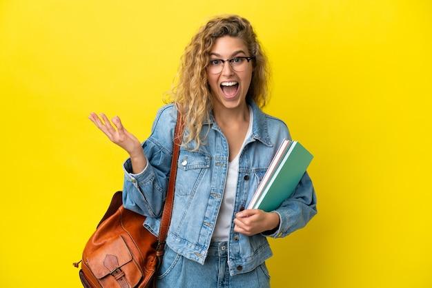 Молодая студентка кавказская женщина изолирована на желтом фоне с шокированным выражением лица