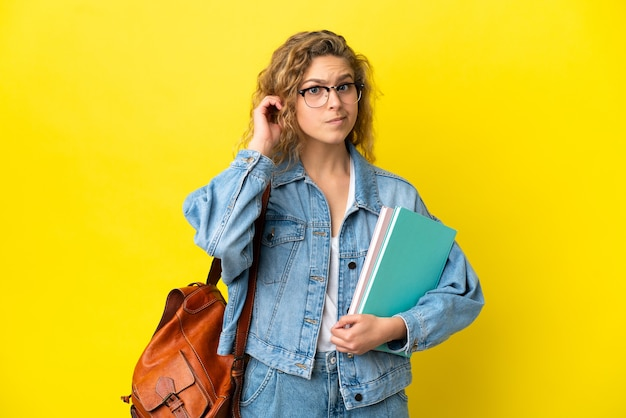 Young student caucasian woman isolated on yellow background having doubts