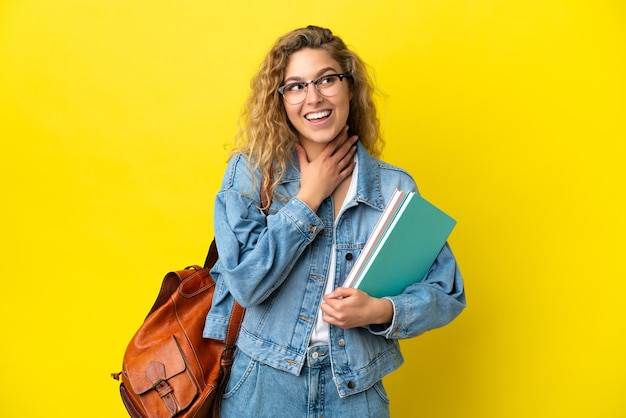 Young student caucasian woman isolated on yellow background looking up while smiling