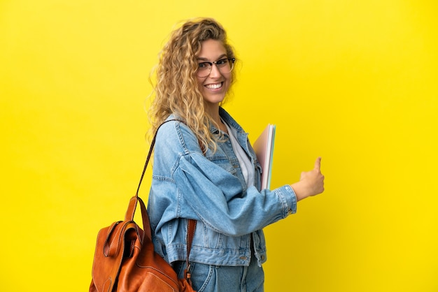 Young student caucasian woman isolated on yellow background pointing back