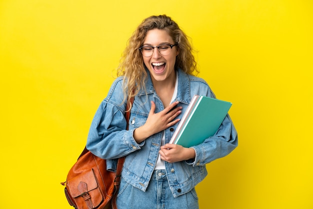 Young student caucasian woman isolated on yellow background smiling a lot
