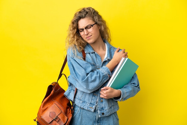 Young student caucasian woman isolated on yellow background suffering from pain in shoulder for having made an effort
