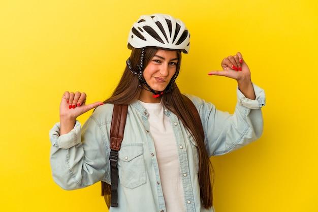 黄色の背景に分離された自転車のヘルメットを身に着けている若い学生の白人女性は、誇りと自信を感じています。