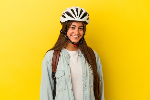 黄色の背景に分離された自転車のヘルメットを身に着けている若い学生白人女性幸せ、笑顔、陽気な。