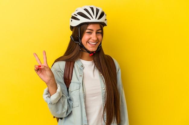 黄色の背景に分離された自転車のヘルメットを身に着けている若い学生の白人女性は、指で平和のシンボルを示して楽しくてのんきです。