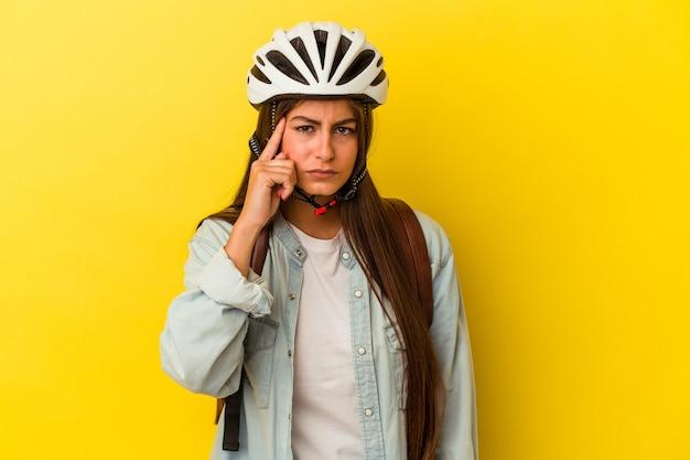 黄色の背景に分離された自転車のヘルメットを身に着けている若い学生の白人女性は、指で寺院を指して、考えて、タスクに焦点を当てた。
