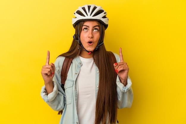 開いた口で逆さまを指している黄色の背景に分離された自転車のヘルメットを身に着けている若い学生白人女性。
