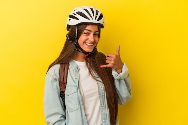 指で携帯電話の呼び出しジェスチャーを示す黄色の背景に分離された自転車のヘルメットを身に着けている若い学生の白人女性。