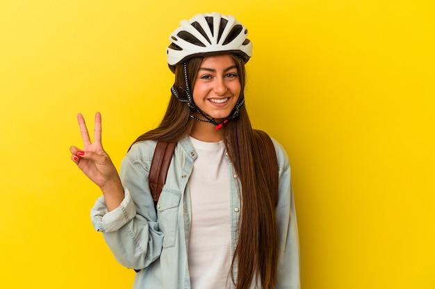 指で2番目を示す黄色の背景に分離された自転車のヘルメットを身に着けている若い学生白人女性。