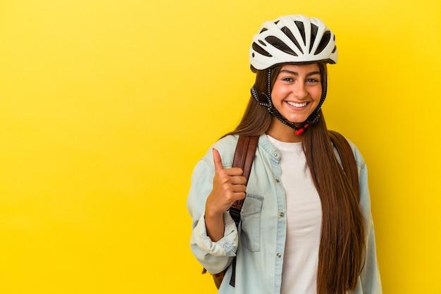 笑顔と親指を上げて黄色の背景に分離された自転車のヘルメットを身に着けている若い学生白人女性