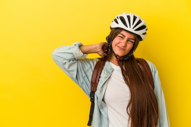 Молодой студент кавказской женщина в велосипедном шлеме, изолированном на желтом фоне, касаясь затылка, думая и делая выбор.