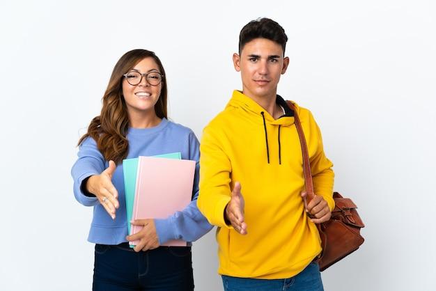 좋은 거래를 닫기 위해 악수하는 흰색에 젊은 학생 커플