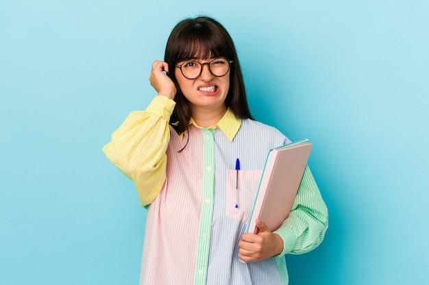 手で耳を覆う青い背景で隔離の本を保持している若い学生の曲がりくねった女性。 Premium写真