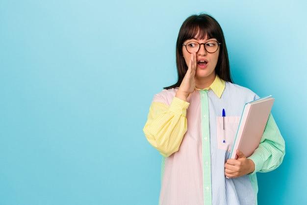 青い背景で隔離の本を保持している若い学生の曲がりくねった女性は、秘密のホットブレーキのニュースを言って脇を見ています