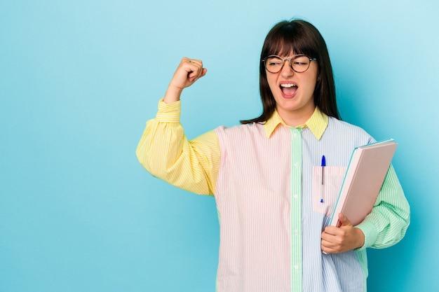 勝利、勝者の概念の後に拳を上げる青い背景で隔離の本を保持している若い学生の曲がりくねった女性。
