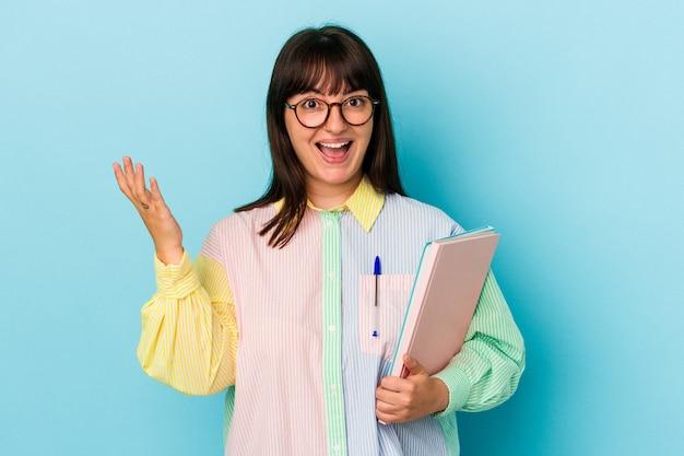青い背景で隔離の本を保持している若い学生の曲がりくねった女性は、嬉しい驚きを受け取り、興奮し、手を上げます。