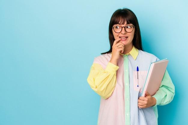 青い背景で隔離の本を保持している若い学生の曲がりくねった女性は、コピースペースを見ている何かについて考えてリラックスしました。
