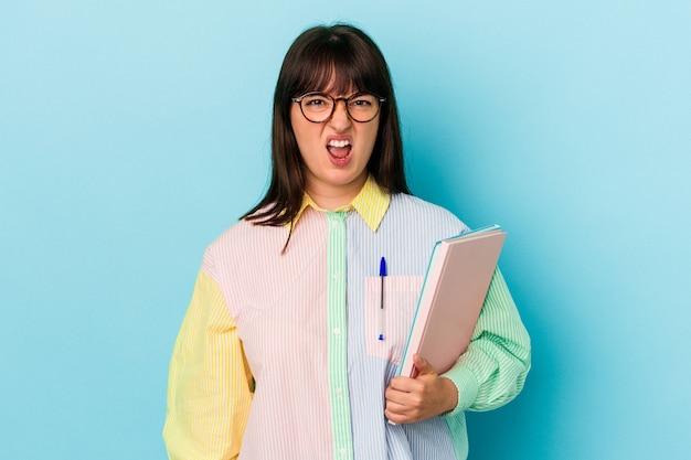非常に怒って攻撃的に叫んで青い背景で隔離の本を保持している若い学生の曲がりくねった女性。