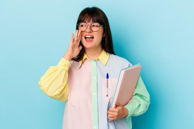開いた口の近くで叫び、手のひらを保持している青い背景で隔離の本を保持している若い学生の曲がりくねった女性。