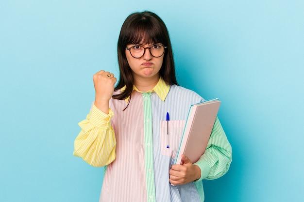 カメラに拳、攻撃的な表情を示す青い背景で隔離の本を保持している若い学生の曲線美の女性。