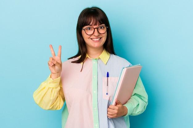 指で2番目を示す青い背景で隔離の本を保持している若い学生の曲がりくねった女性。