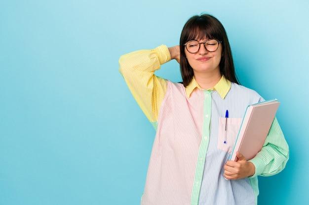 頭の後ろに触れて、考えて、選択をする青い背景で隔離の本を保持している若い学生の曲がりくねった女性。