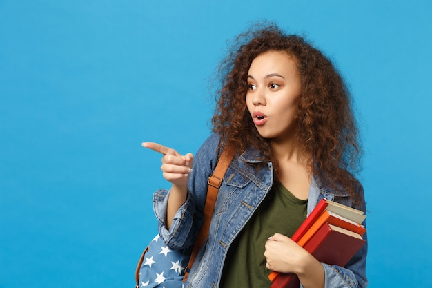 Young student in denim clothes and backpack holds books isolated on blue wall