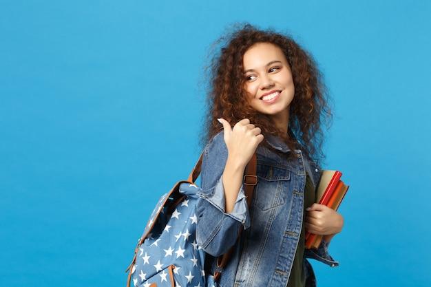 Il giovane studente in vestiti e zaino del denim tiene i libri isolati sulla parete blu
