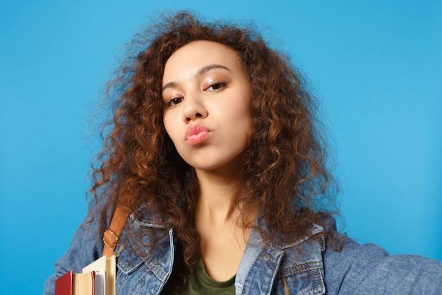 Young student in denim clothes and backpack holds books, sends kiss and makes selfie photo isolated on blue wall