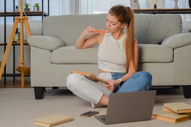 Молодой студент делает домашнее задание после лекции фрилансер работает за компьютером